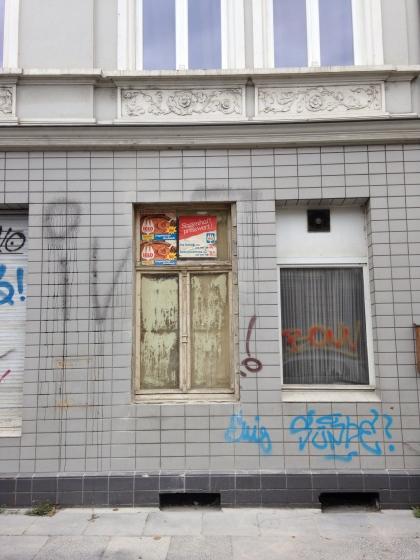 Foto eines Gebäudes mit Graffiti und zugeklebten Fensterscheiben